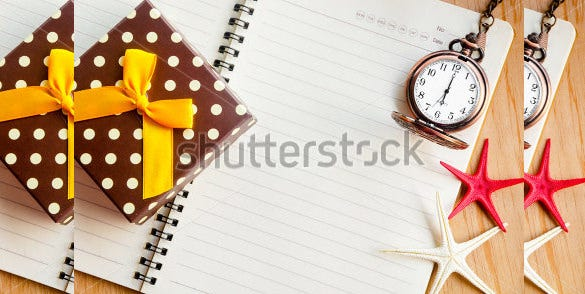 open diary and pocket watch with gift box on wooden background