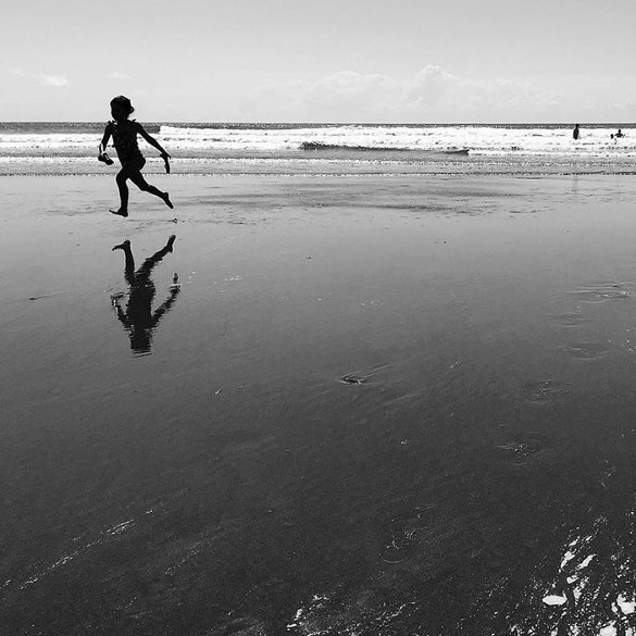 kid running on beach reflective photography