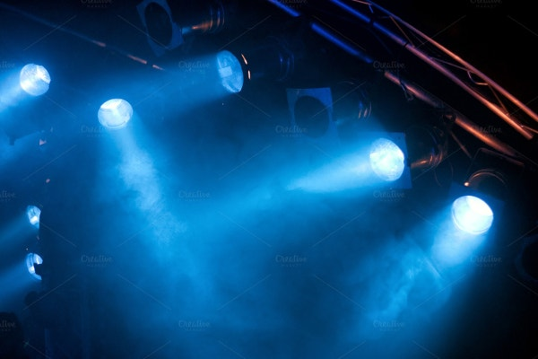several blue stage lights in the dark background