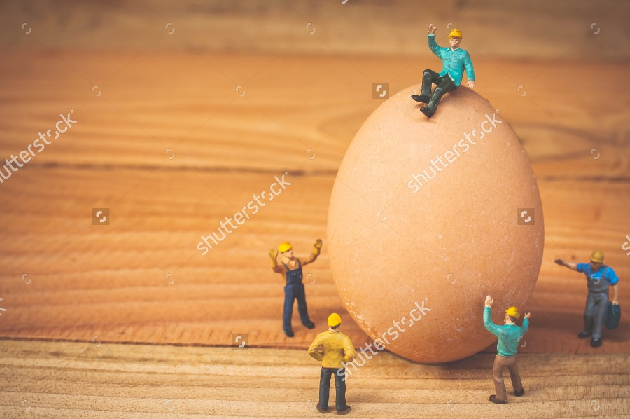 miniature-people-sitting-on-egg