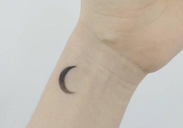 minimalist style moon tattoo on the wrist